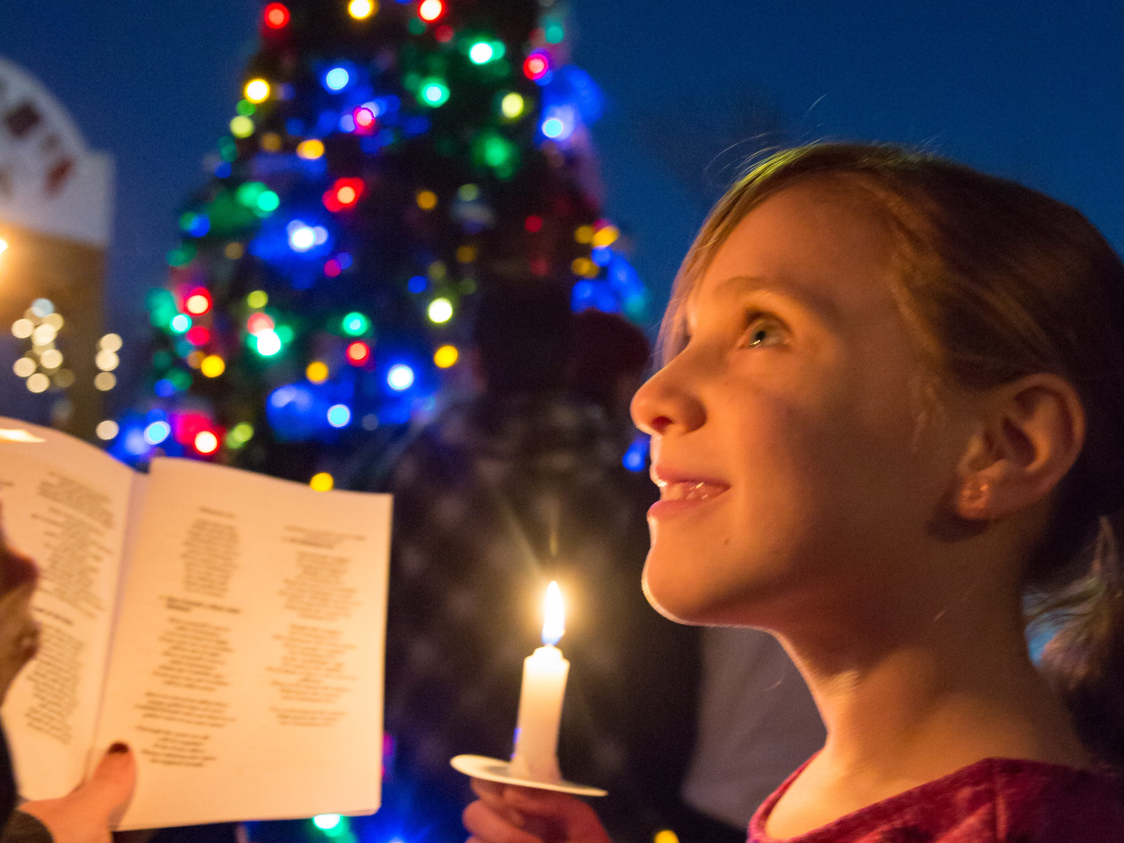 Ana Barela, 7, of Las Cruces, sing carols  at the Mesilla Plaza on Christmas Eve, Monday, Dec. 24, 2018. There were 6,000 luminarias lit by the historic village of Old Mesilla.