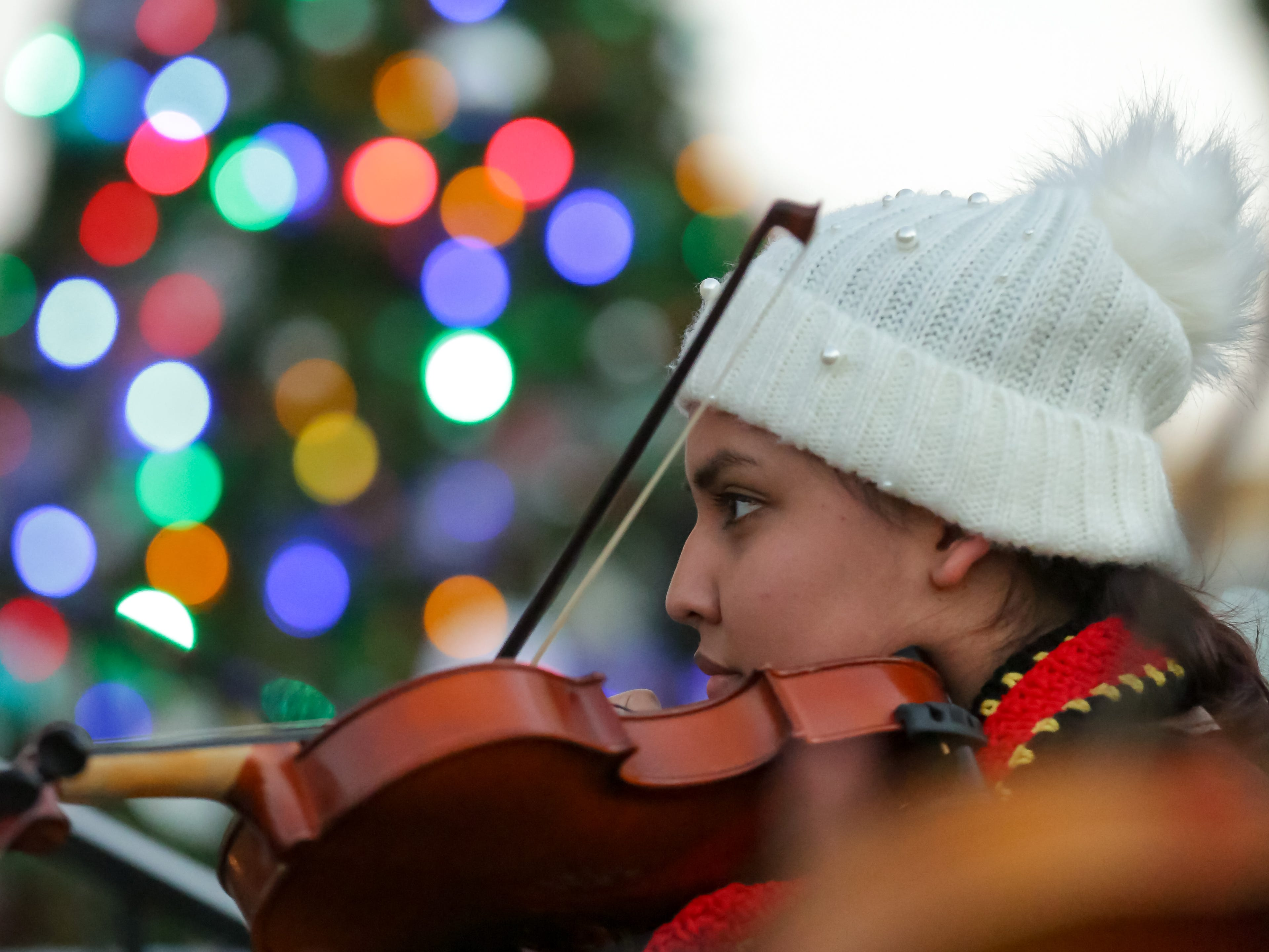 Cinthia Valdez, with Mariachi Aguilas, tunes her violin on Monday, Dec. 24, 2018 at the Mesilla Plaza.