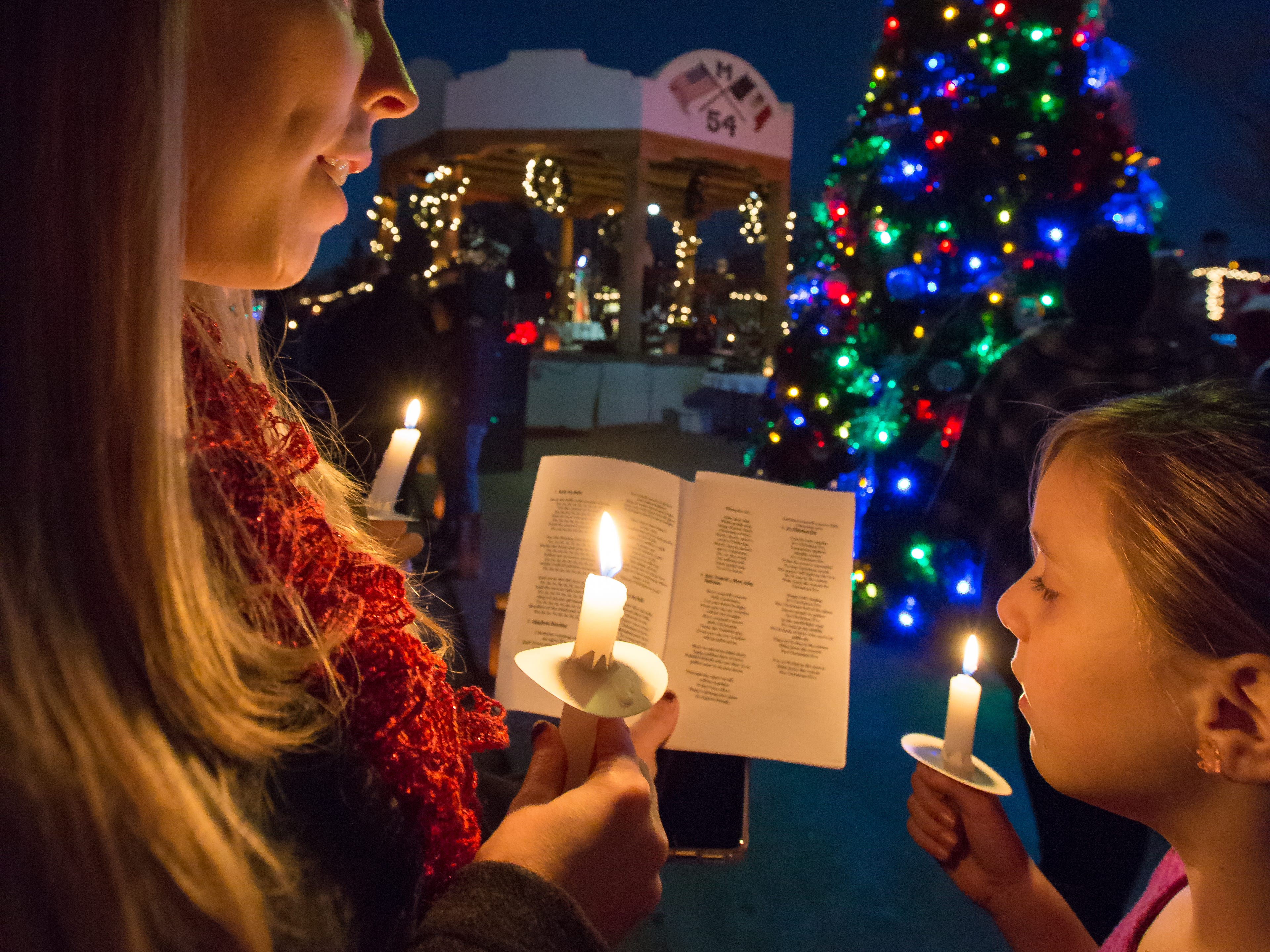 Christine Barela, and her daughter Ana, 7, of Las Cruces, sing carols during a Christmas Eve celebration onthe Mesilla Plaza on Monday, Dec. 24, 2018. Thousands attended to event to sing carols, browse shops and drink hot cocoa surrounded by6,000 luminarias along the streets of Mesilla.