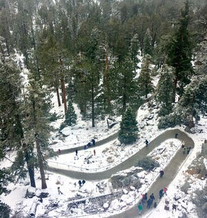 Visitors stroll atop Mount San Jacinto on Christmas morning. Some 2 inches of snow fell on the mountain on Tuesday.