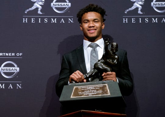 FILE - In this Dec. 8, 2018, file photo, Oklahoma quarterback Kyler Murray holds the Heisman Trophy after winning the award in New York. The latest statistical surge has been led by the quarterbacks who will play in the Orange Bowl semifinal on Jan. 29, when No. 1 Alabama faces No. 4 Oklahoma. Both Heisman Trophy winner Murray (205.72) of Oklahoma and Alabama's Tua Tagovailoa (202.30) are on pace to break the record for passer efficiency rating set by former Sooners quarterback Baker Mayfield (198.92) last season. (AP Photo/Craig Ruttle, File)