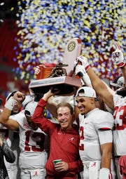 Alabama head coach Nick Saban and Alabama quarterback Jalen Hurts, right, celebrate with the team after the Southeastern Conference championship NCAA college football game against Georgia, Saturday, Dec. 1, 2018, in Atlanta. Alabama won 35-28. (AP Photo/John Bazemore)