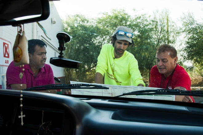 Scott Warren (in center) a volunteer leader of the humanitarian group No More Deaths, along with Irineo Mujica (on left) and Rafael Larraenza Hernandez, look at the map where they will go to search for the remains of migrants crossing the U.S. border illegally in triple-digit temperatures through the Organ Pipe Cactus National Monument near Ajo, Arizona.