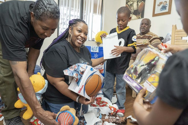 Dana Burns brought toys and a Christmas meal to Nylayia Richards, 3 and Chrishawn Thomas, 6, whose brother died after being hit by a car in December. Burns and her partner, Jamal Carter brought the meal and toys on behalf of their non-profit group, the Permanent Voice Foundation, which aims to help people face daunting obstacles, whether poverty, family separation or illness.