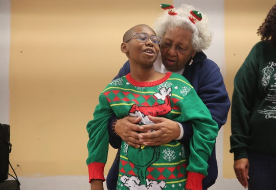 Tracey Daniels Jr., left, 11, of the City of Poughkeepsie, protests for a moment as his grandmother, Doris Brown, right, urges him to sing during the Eileen Hickey Holiday Christmas dinner.