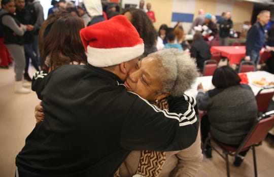 Volunteer Mae Parker Harris (right) hugs organizer Frankie Flowers (left) during the annual Eileen Hickey Holiday Dinner on Christmas. She said many people come for the feeling of community, and to socialize.
