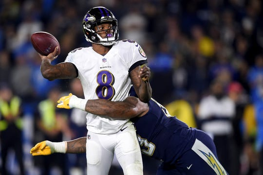 FILE - In this Dec. 22, 2018, file photo, Baltimore Ravens quarterback Lamar Jackson passes under pressure from Los Angeles Chargers defensive tackle Darius Philon during the first half in an NFL football game in Carson, Calif.