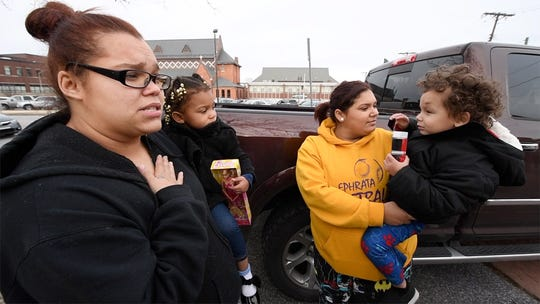 "Kira Tomoney, left, said the gift giveaway was ""really good for the kids."" Tomoney, who's a single mother of two, is holding her daughter, Jazzabella, 2. Tomoney is standing with her sister, Katiria, who's holding her nephew, Vincent, 3."