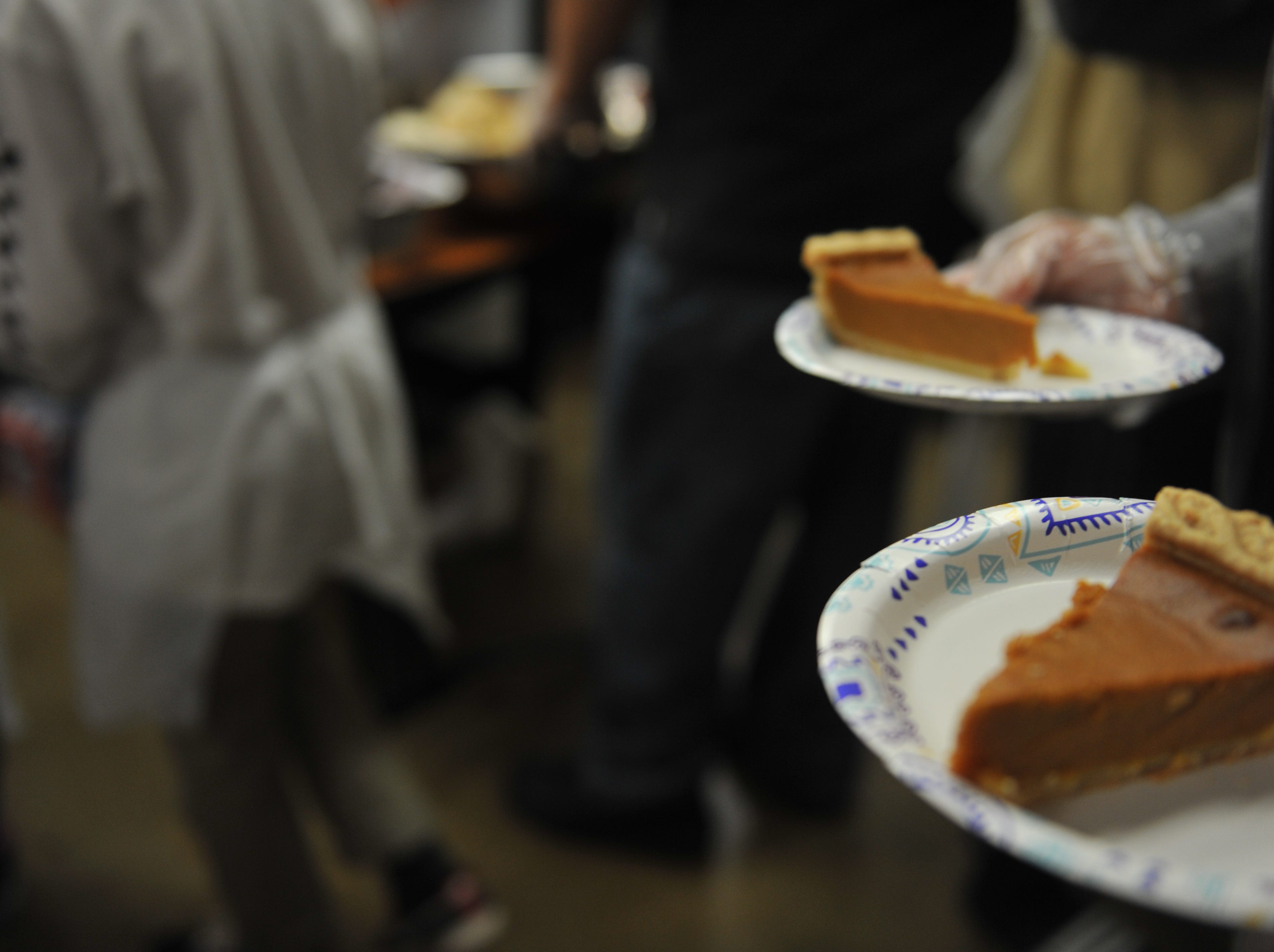 A volunteer serves pumpkin pie at OMNI's Christmas lunch.