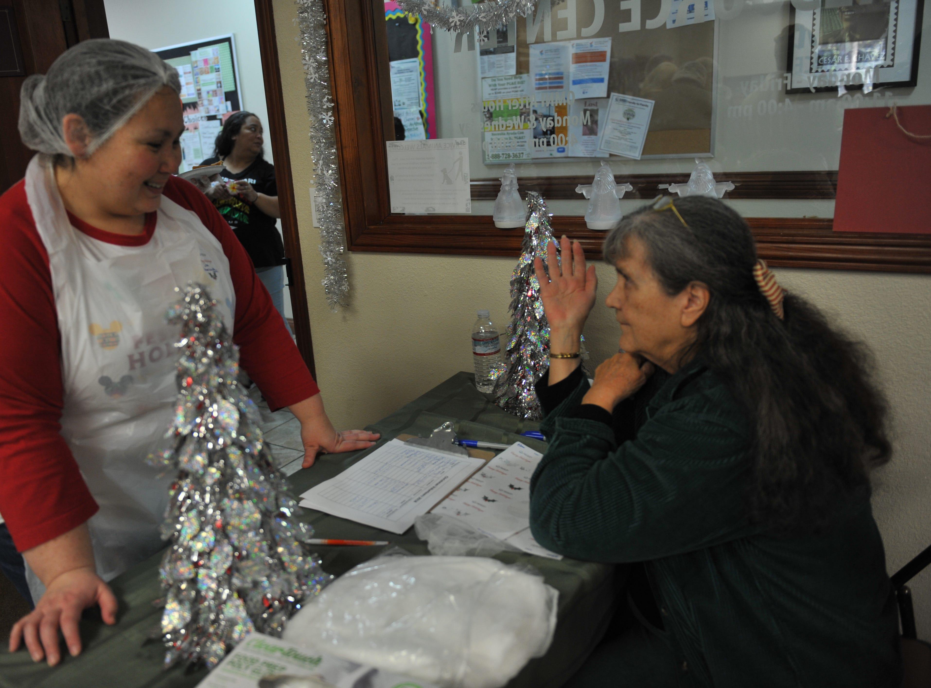 OMNI Administrator Lisa Corpuz, left, speaks with a volunteer.