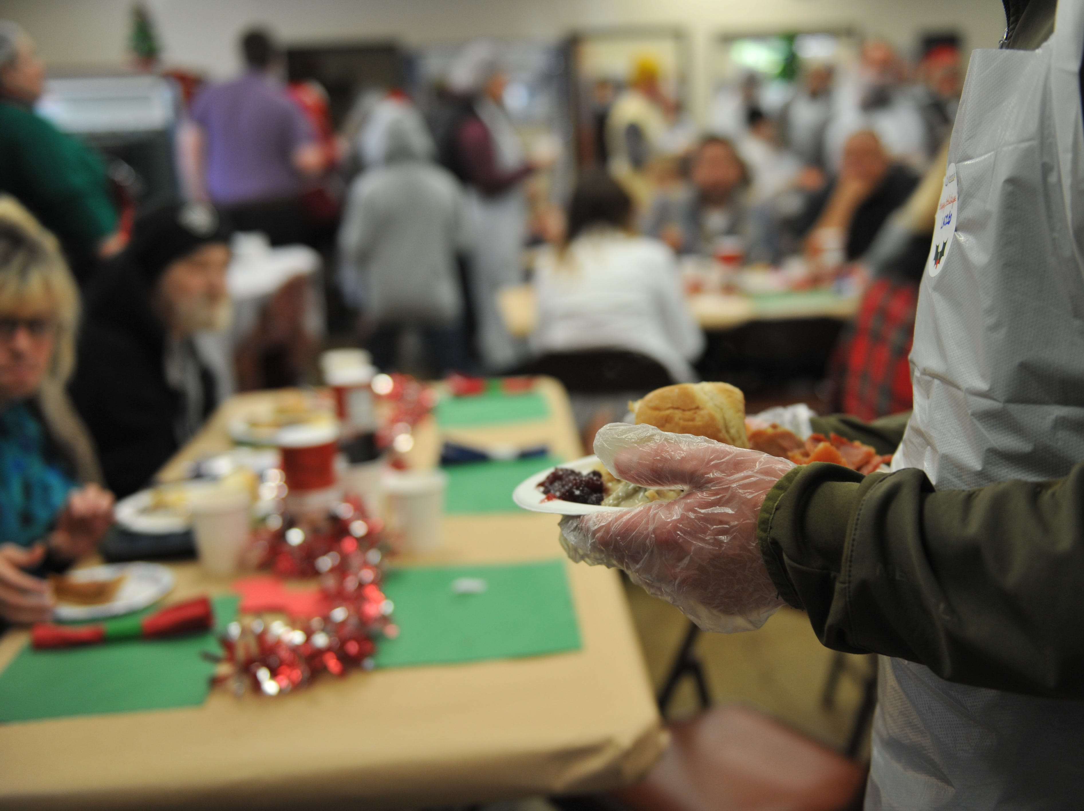 A volunteer brings out a meal at the OMNI center on Christmas.