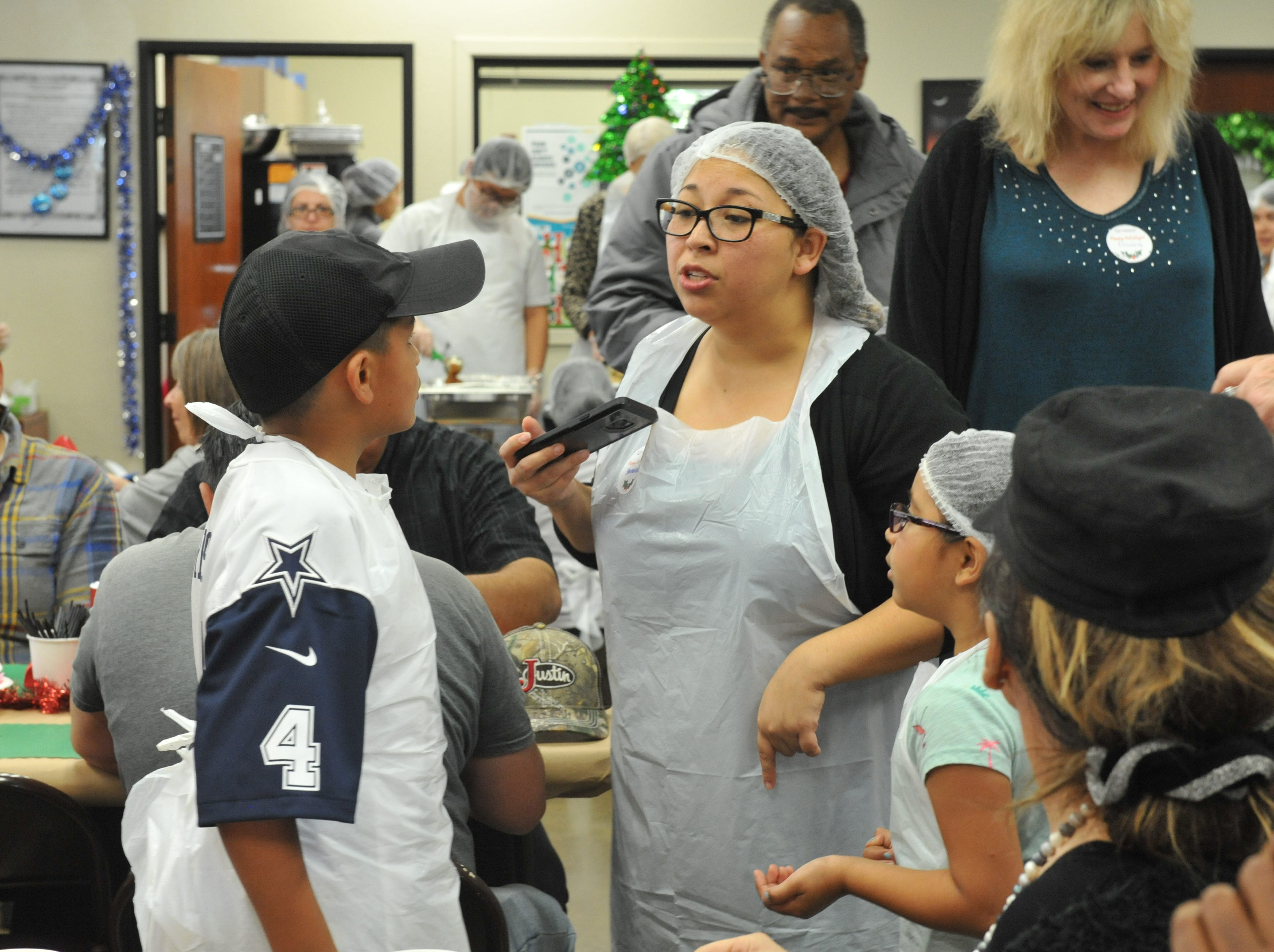 Savannah Alvarez speaks to two young volunteers at the holiday meal on Tuesday, Christmas Day.