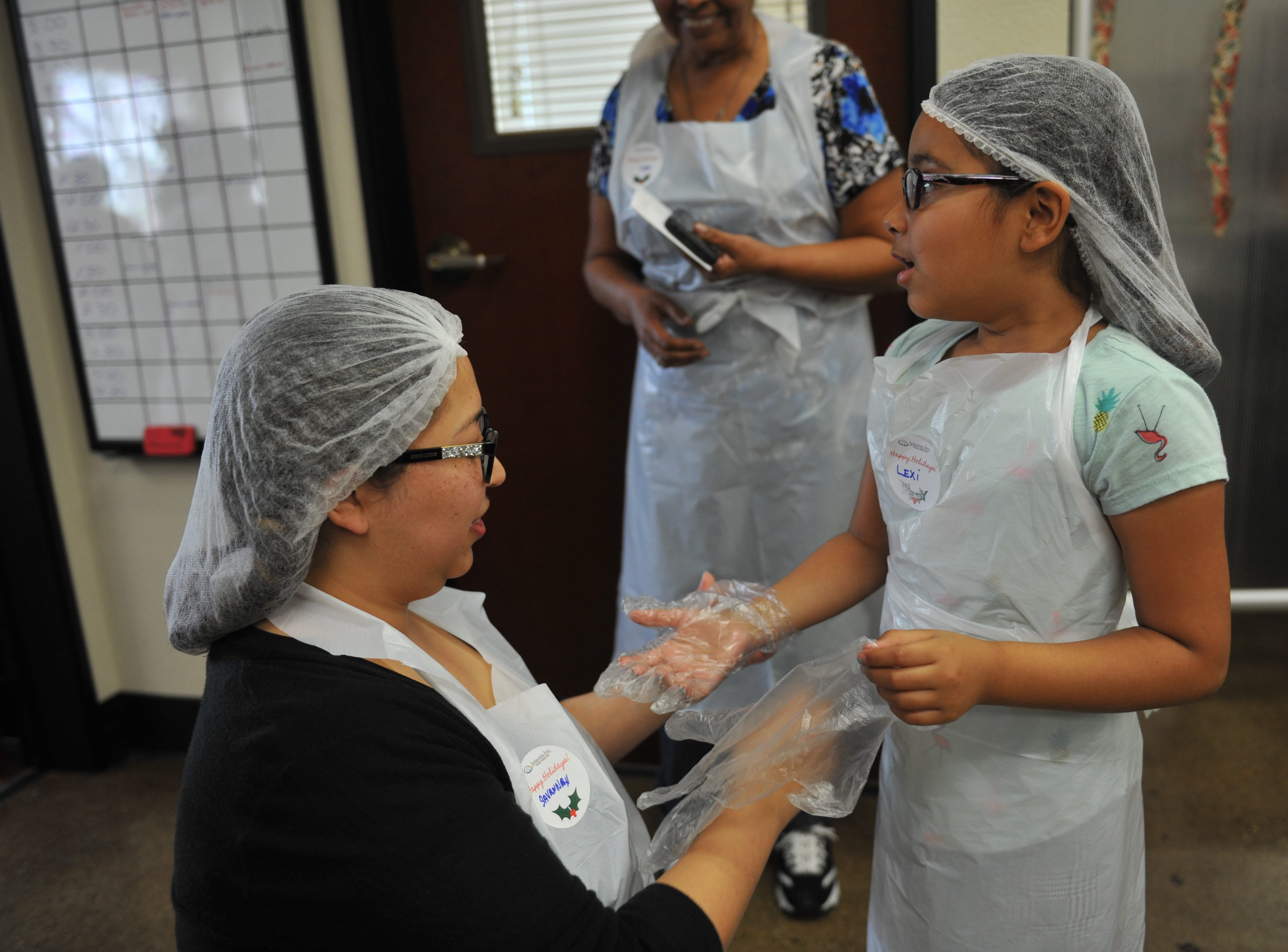 With Savannah Alvarez putting on her gloves, a young volunteer gets ready to serve more holiday meals at the OMNI Resource Center.