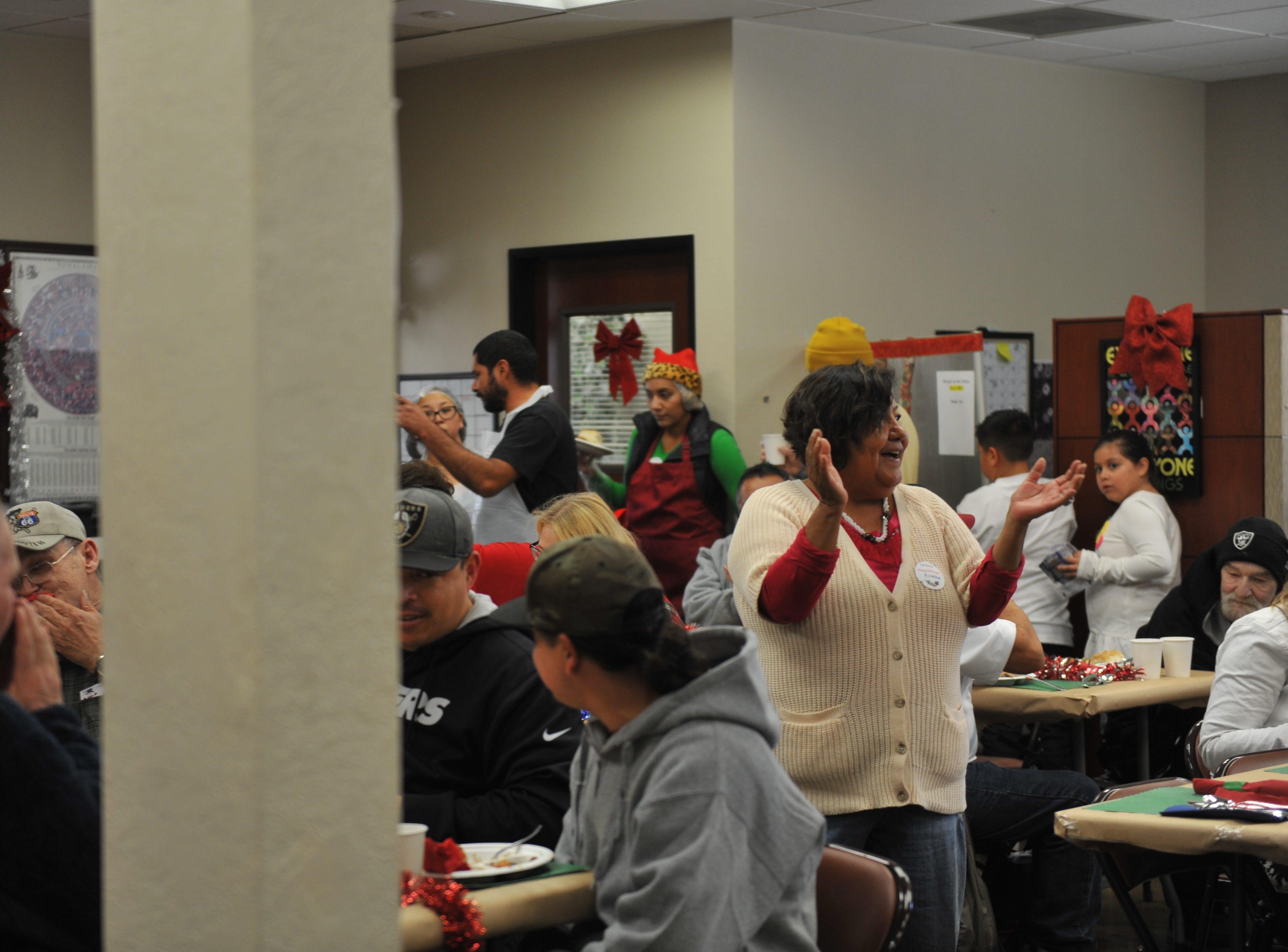 """Volunteer Ricarda Rodriguez leads attendees and volunteers in singing """"Feliz Navidad"""" at Interim, Inc.'s Christmas meal at the OMNI center in Salinas."""