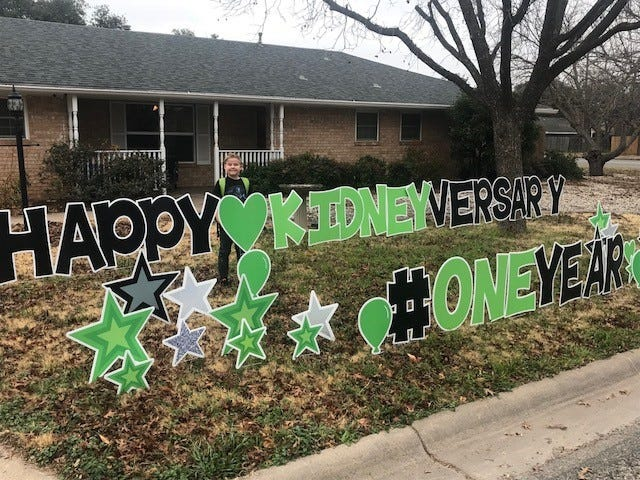 "Canyon Martin behind his ""Happy Kidneyversary"" sign at the family's home Dec. 25, 2018. Canyon, 12, received a kidney transplant on Christmas Eve 2017."