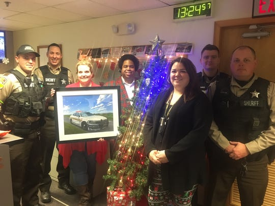 Augusta County deputies and emergency communication center employees stand together on Christmas Day 2018. Sgt. Patrick Fuchs gifted them a copy of his sheriff's office cruiser oil painting.