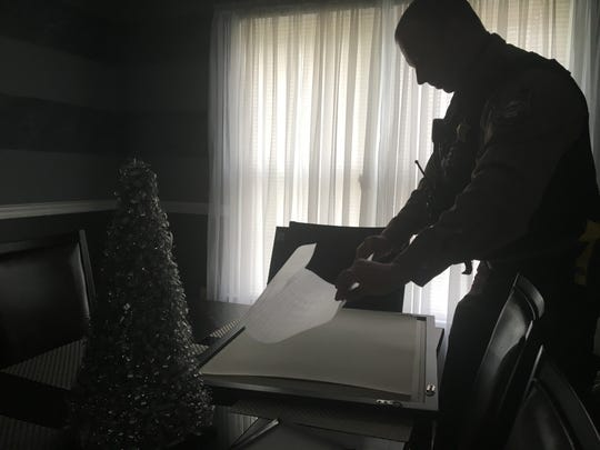 Sgt. Patrick Fuchs carefully frames a copy of an oil painting he created to gift to the Augusta County Emergency Communication Center.