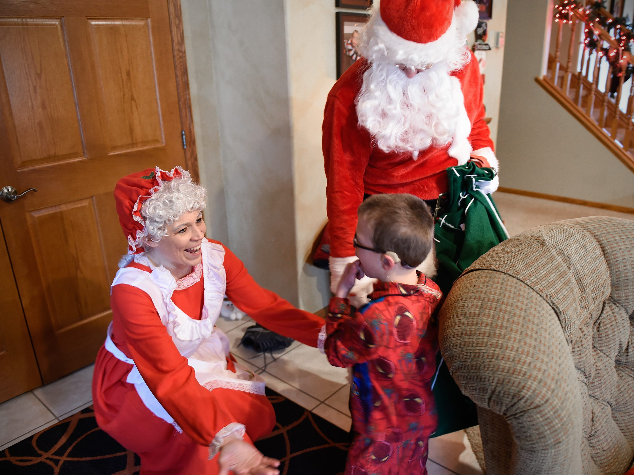 Camran Schneider, 6, gives Mrs. Claus a hug Tuesday, Dec. 25, at his home in Kimball.