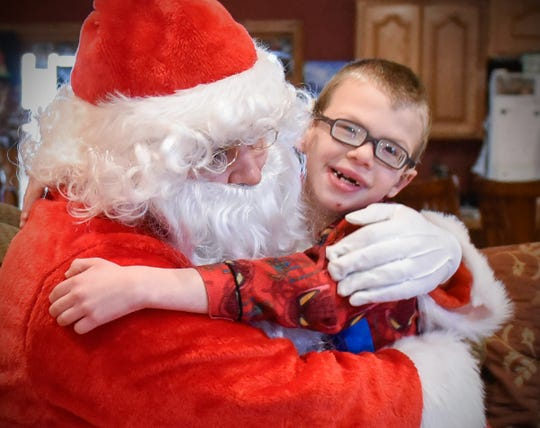 Camran Schneider, 6, gives Santa a big hug after opening his presents Tuesday, Dec. 25, at his home in Kimball.