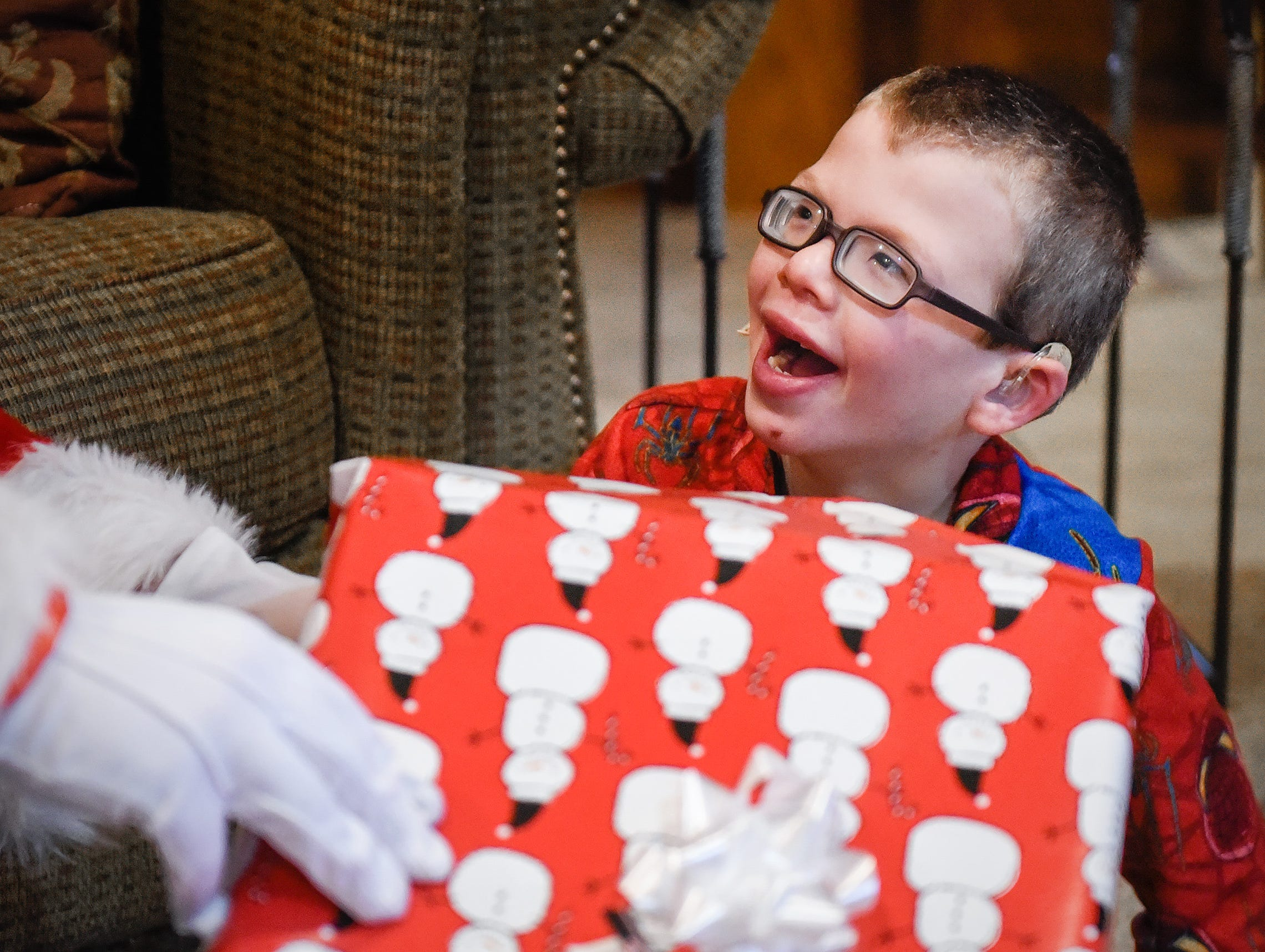 An excited Camran Schneider, 6, gets a gift from Santa and Mrs. Claus Tuesday, Dec. 25, at his home in Kimball.