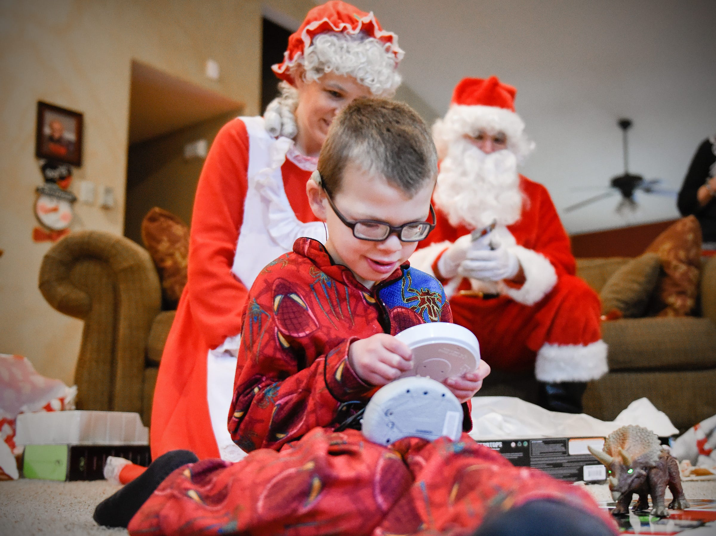 Camran Schneider, 6, plays with an adapted remote control dinosaur which was a special delivery Tuesday, Dec. 25, by Santa and Mrs. Claus to the Schneider home in Kimball.