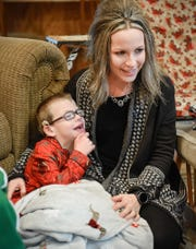 Camran Schneider, 6, sits with his mom Stacie as Santa and Mrs. Claus hand out presents during a special stop Tuesday, Dec. 25, in Kimball.