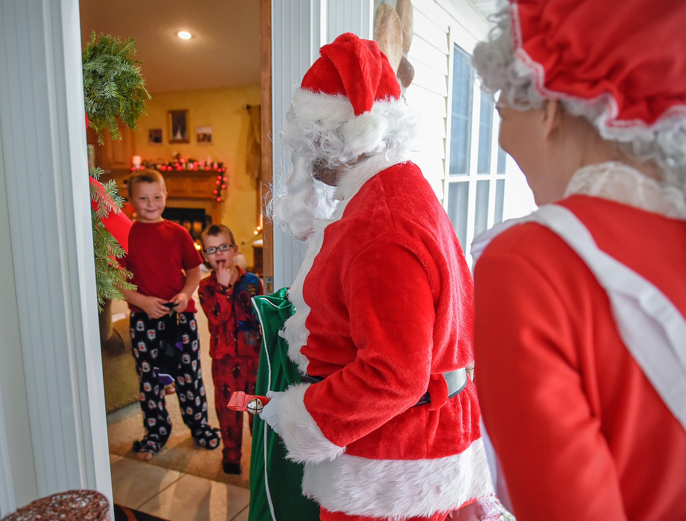 Landon Schneider, 8, and his brother Camran, 6, open the door to find Santa and Mrs. Claus Tuesday, Dec. 25, during a surprise visit to their home in Kimball.