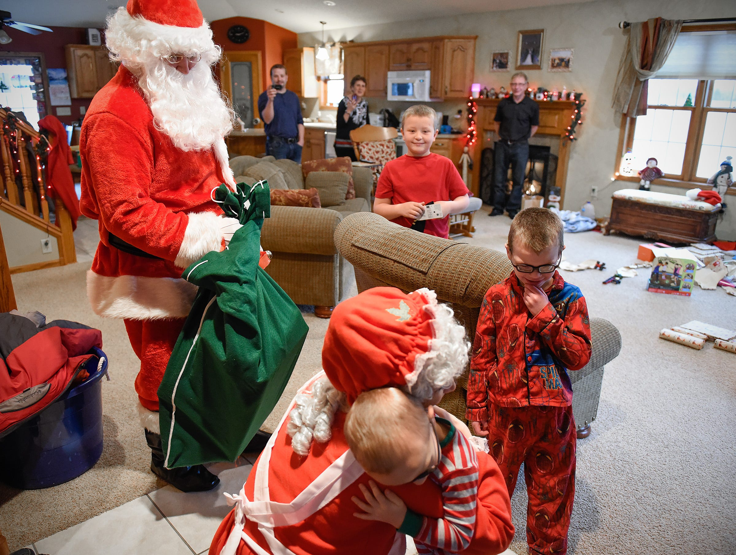 Santa and Mrs. Claus get hugs from Brockdan Schneider, 3, Landan, 8, center, and Camran, 6, during a special stop Tuesday, Dec. 25, in Kimball.