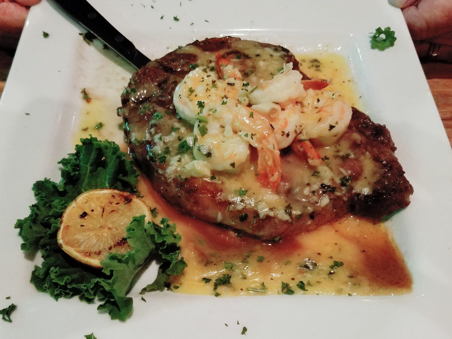Twisted Tuna's Angus rib-eye steak  topped with shrimp scampi in a rich garlic, butter and wine sauce.