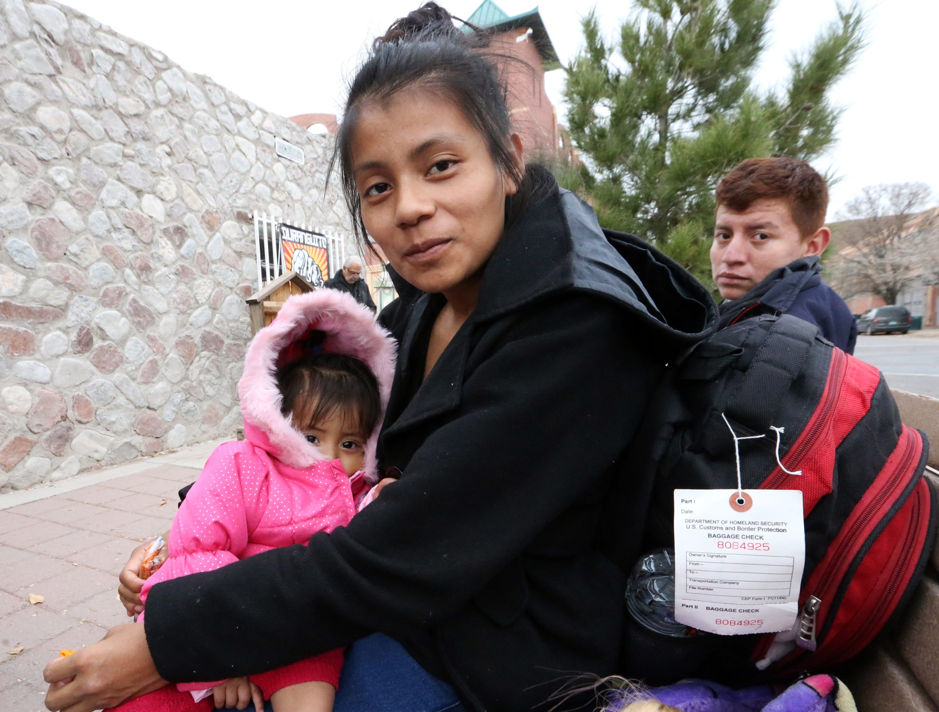 Juana Juan Diego said she left Guatemala City 20 days ago with her 1-year-old daughter, Dulce Juan Diego, as they sit outside the former Rock House Cafe and Gallery at Leon Street and Overland Avenue on Christmas Day. She was one of a group of 100 immigrants dropped off there by U.S. Immigration and Customs Enforcement.  She hopes to travel to Tennessee where she has relatives, she said. She has a baggage-check tag on her backpack from U.S. Customs and Border Protection.