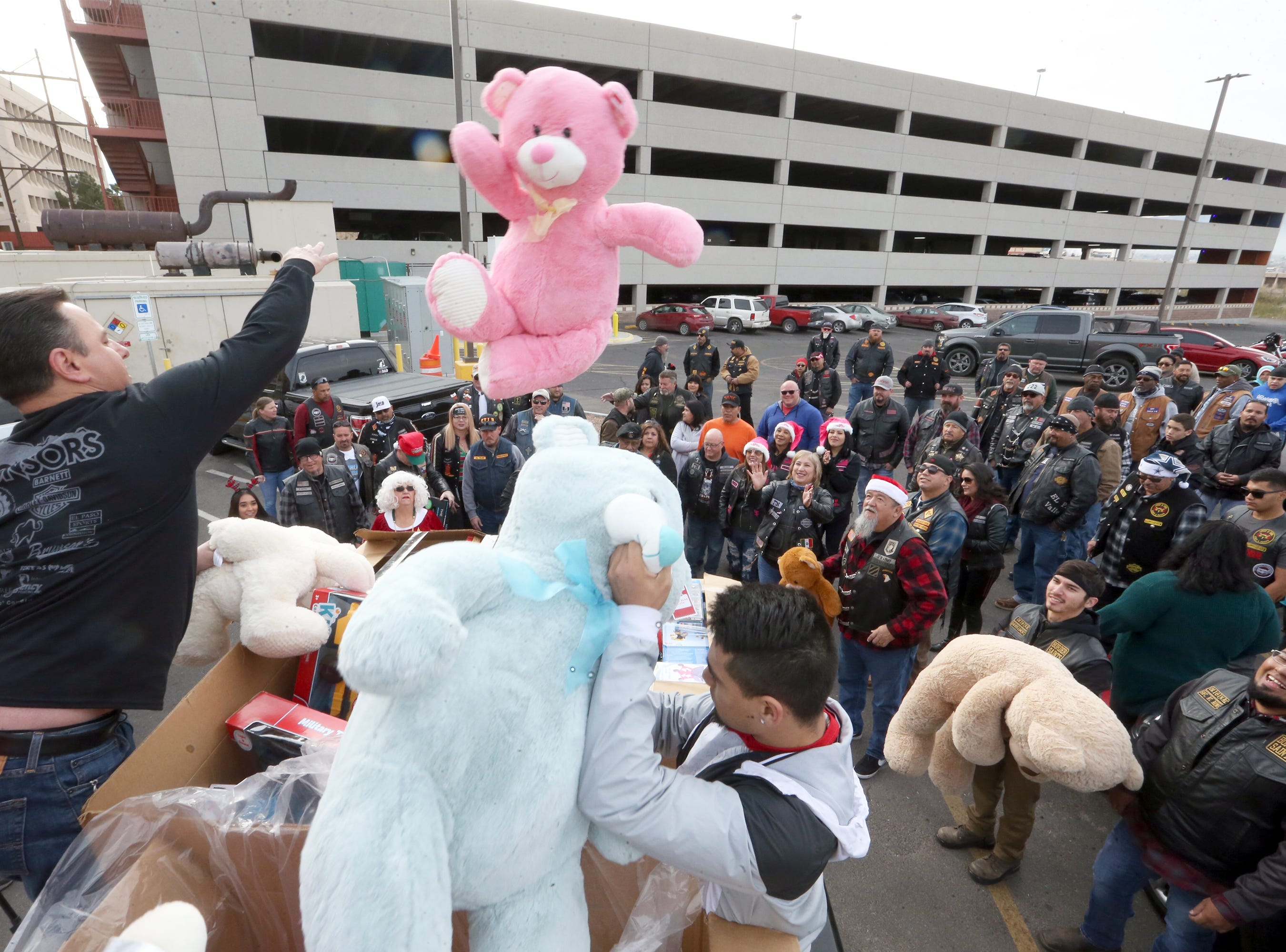 A pink stuffed bear flies throught he air as a truck full of toys is unloaded during the 36th annual Toy Run/Parade toy delivery put on by the El Paso Motorcycle Coalition at Providence Children's Hospital on Christmas Day Tuesday.