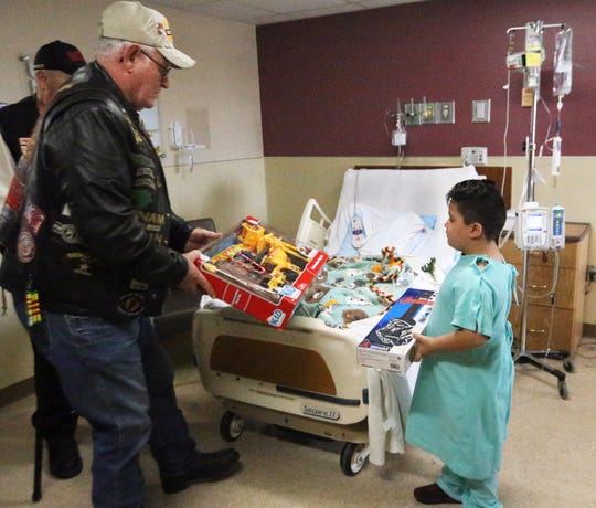 Hal Depuy, left, of the Legion Riders 58th Chapter, hands a toy to 5-year-old Iker Barajas on Tuesday at Providence Children's Hospital.