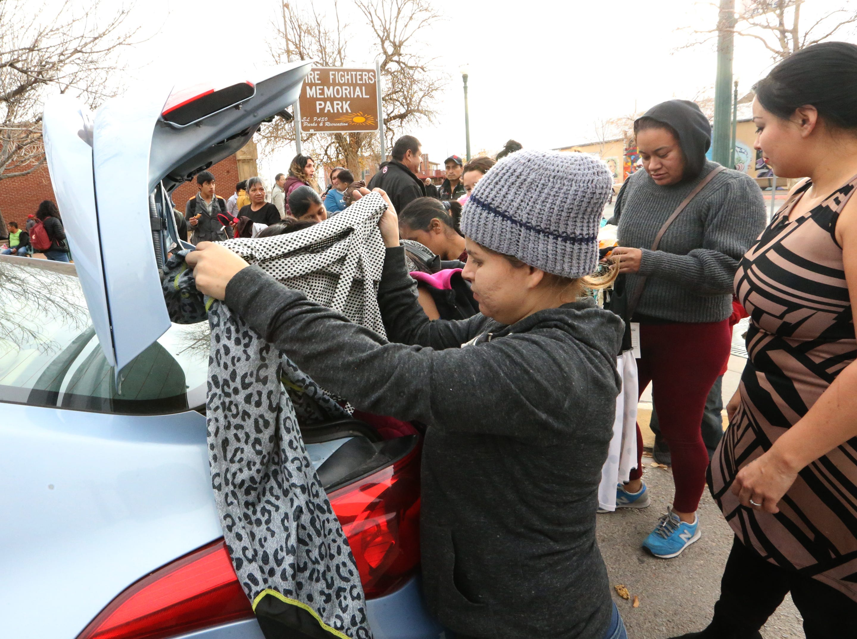 Migrants look at cloths being given from the back of a car along Overland Ave. and Leon Street Tuesday.
