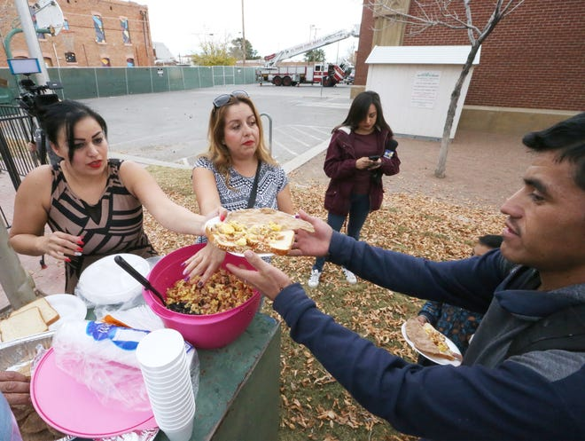 Cynthia Muñiz, left, and her sister, Michaelle Sanchez, serve meals to migrants Tuesday in Fire Fighters Memorial Park at Overland Avenue and Leon Street. One hundred migrants were dropped off near there by U.S. Immigration and Customs Enforcement, said Dylan Corbett, executive director of the Hope Border Institute.