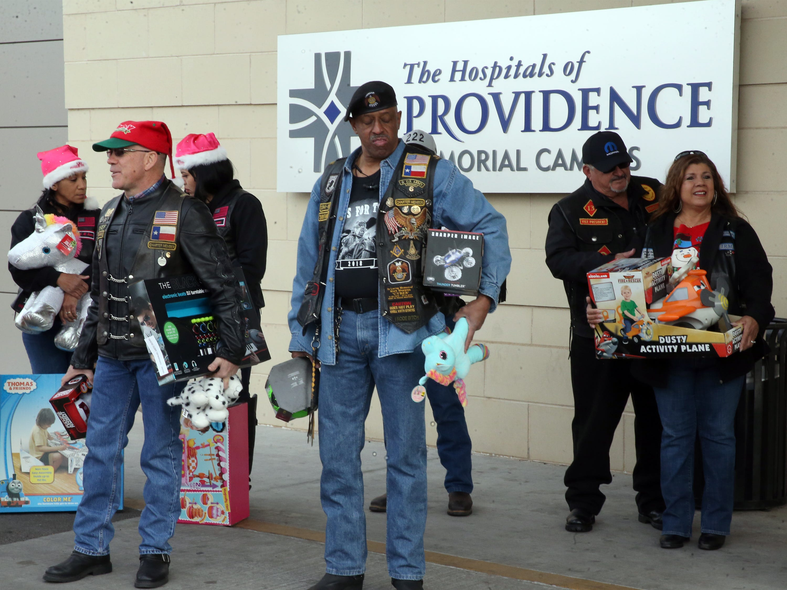Members of the El Paso Motorcycle Coalition wait to enter Providence Children's Hospital with toys in hand Christmas Day Tuesday. The toys were recently collected during the group's annual Toy Run/Parade.