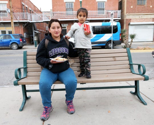 Senaida Areli Deras Villeda and her 3-year-old daughter Francisca Dayani Portillo of Honduras eat a meal given to them at Fire Fighters Memorial Park at Leon St. and Overland Ave. Tuesday. They were among 100 migrants dropped off nearby by Immigration and Customs Enforcement. Deras said she plans to travel to Tennessee to rejoin her husband.