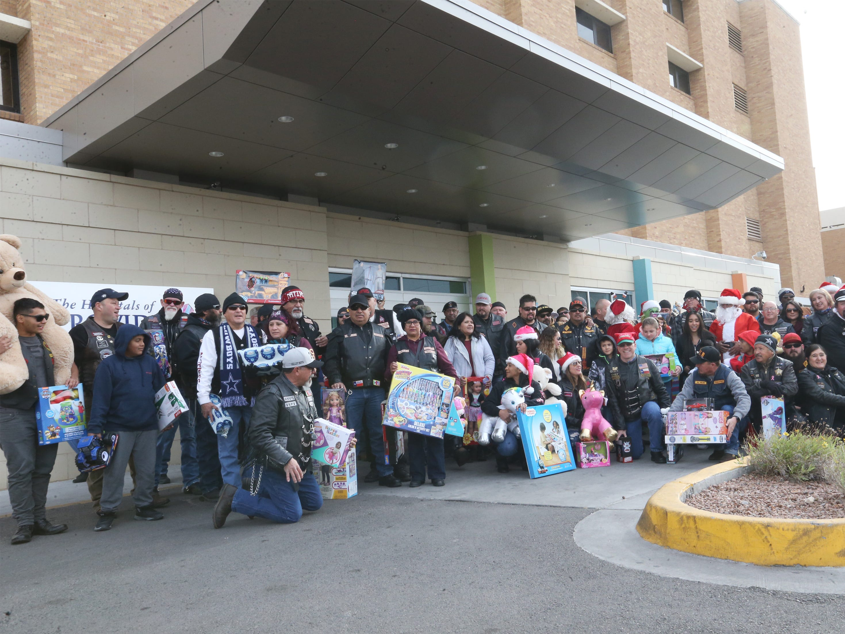 Members of the El Paso Motorcycle Coalition pose for photos with toys outside Providence Children's Hospital on Christmas Day.