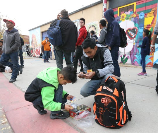 Jose Manuel Perez of Guatemala plays with his son, Sancer Perez, 9, outside the former Rock House Café and Gallery at Leon Street and Overland Avenue. Perez said they left Guatemala 12 days ago and plan to travel to Atlanta to join relatives there.