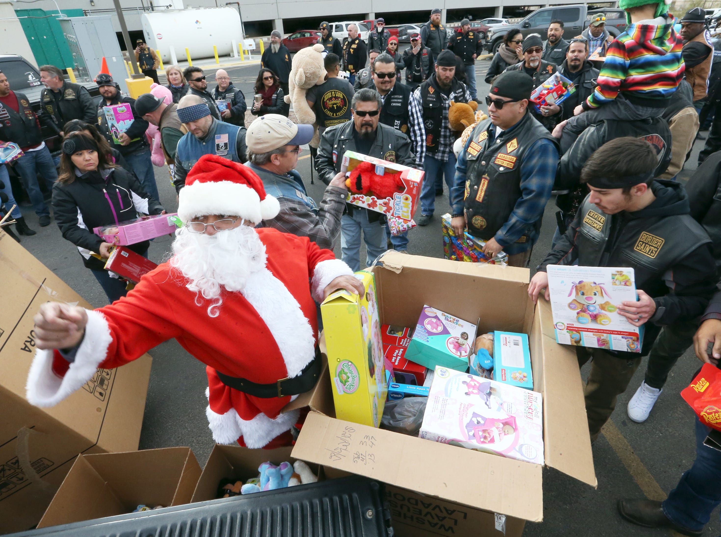 Santa Claus helps distribute toys to members of the El Paso Motorcycle Coalition, so they can hand them out to children during the 36th annual Toy Run/Parade toy delivery at Providence Children's Hospital on Christmas Day.