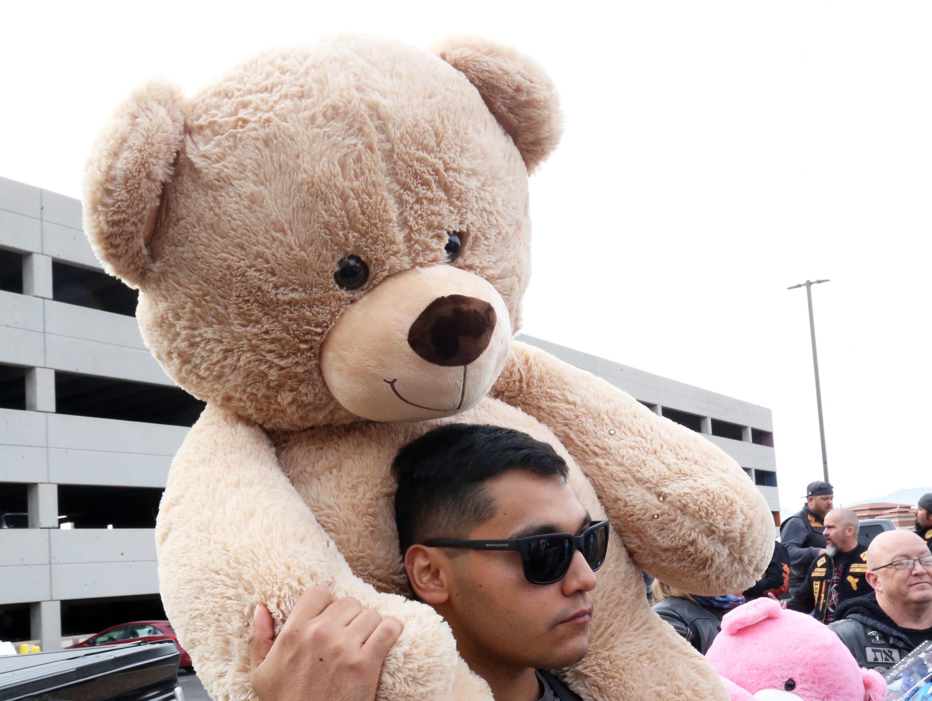 Joseph Saucedo carries in a giant stuffed bear Tuesday.