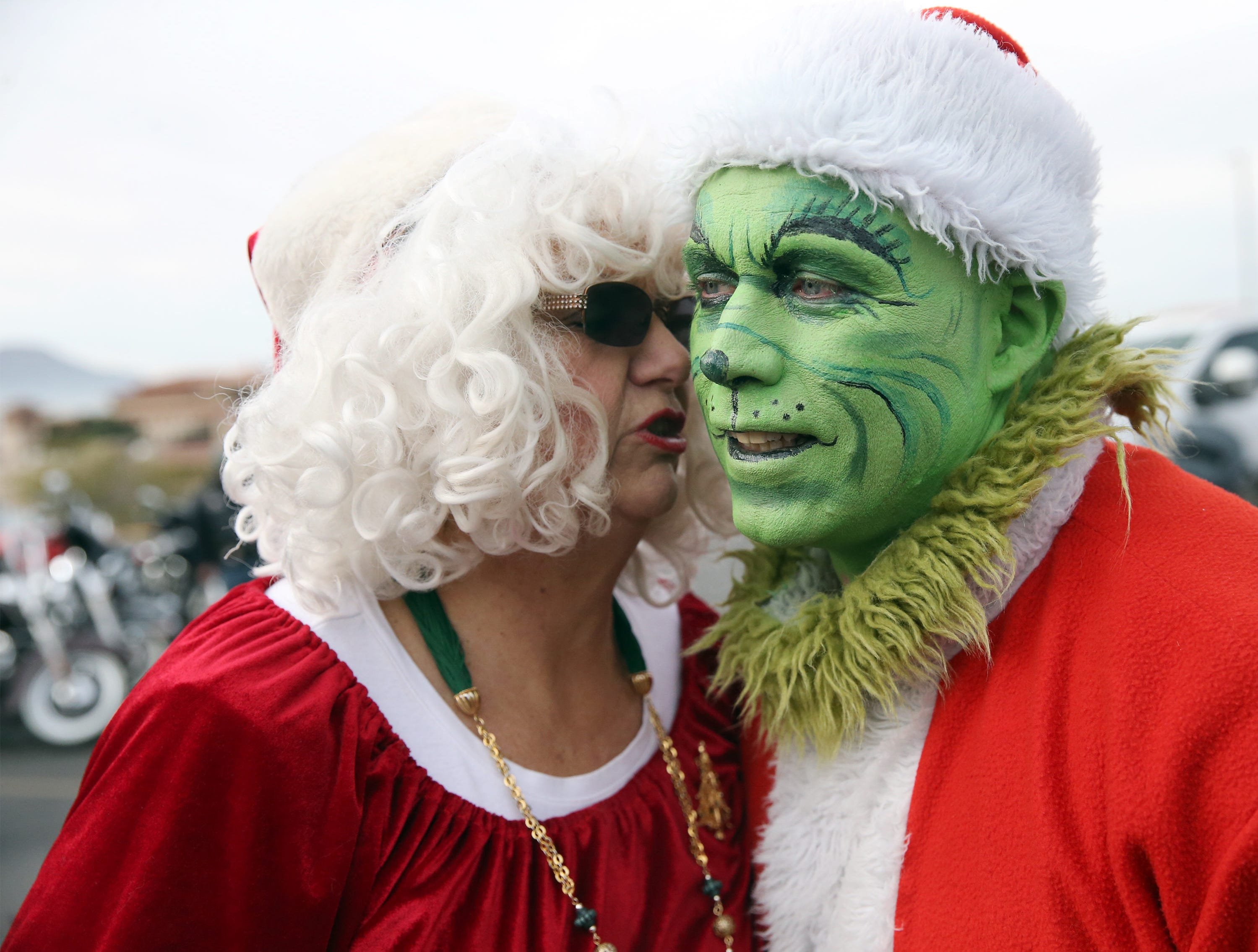 Mrs. Claus sneaks a kiss to the Grinch outside Providence Children's Hospital Christmas Day Tuesday.