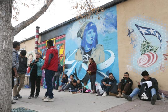 Immigrants, many from Guatemala and other countries, sit outside the former Rock House Cafe and Gallery at Leon Street and Overland Avenue on Tuesday in El Paso, Texas.