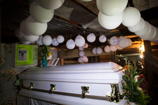 Balloons hang over the coffin that contains the remains of 7-year-old Jakelin Caal Maquin during a memorial service in her grandparent's home Monday, Dec. 24, 2018, in San Antonio Secortez, Guatemala. The body of the girl who died while in the custody of the U.S. Border Patrol was handed over to family members in her native Guatemala on Monday for a last goodbye.