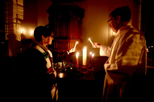 Rev. Jeff Gargano  and Rev. Julia Doellman-Brown light candles during a family Christmas Eve service at the Old Dutch Church in Sleepy Hollow Dec. 24, 2018. A children's choir led the congregation in carols and participated in the service by acting out the parts in the telling of the story of the birth of Jesus.