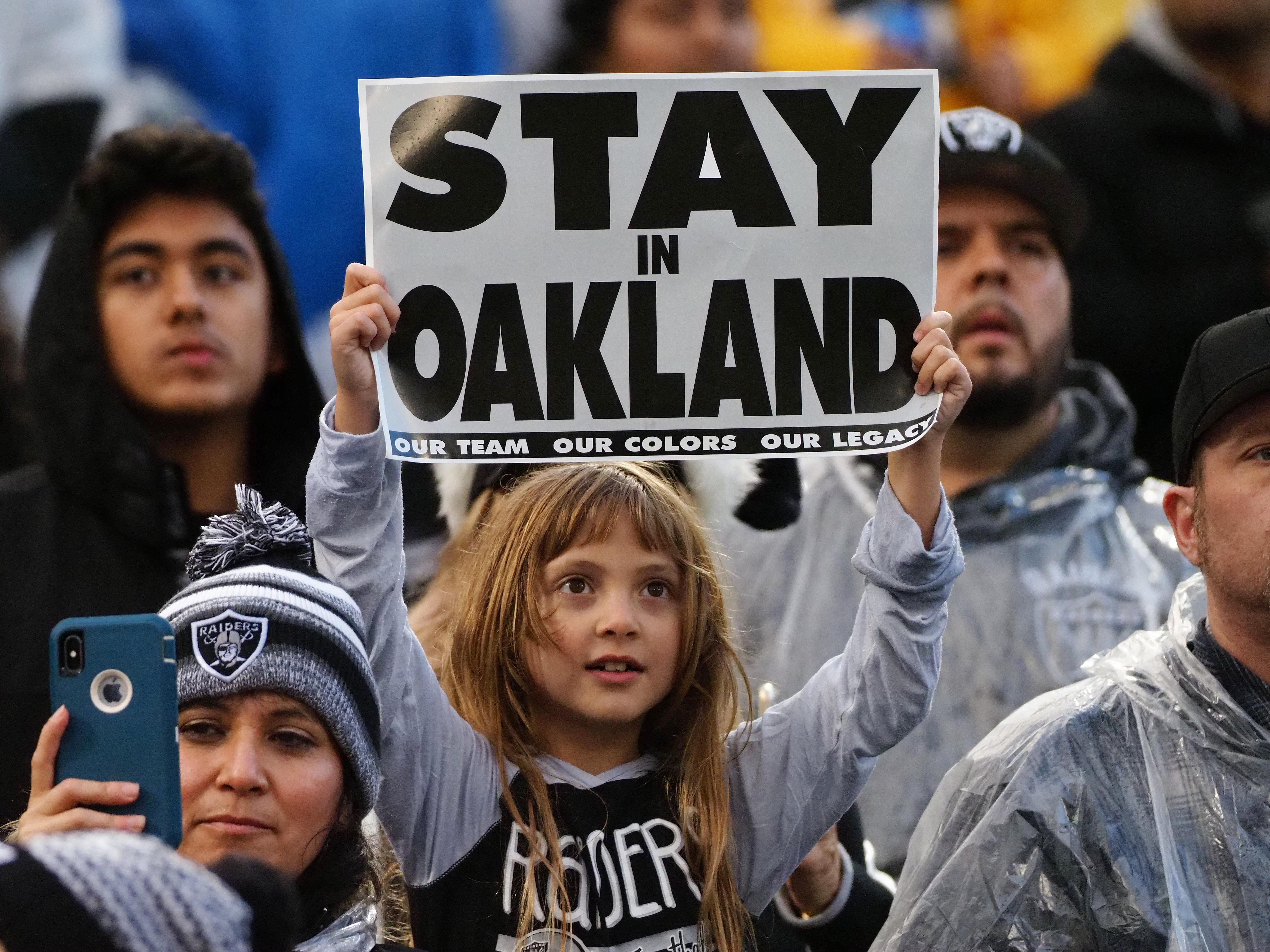 """An Oakland Raiders fan holds a """"Stay in Oakland"""" sign before the game against the Denver Broncos at Oakland Coliseum."""