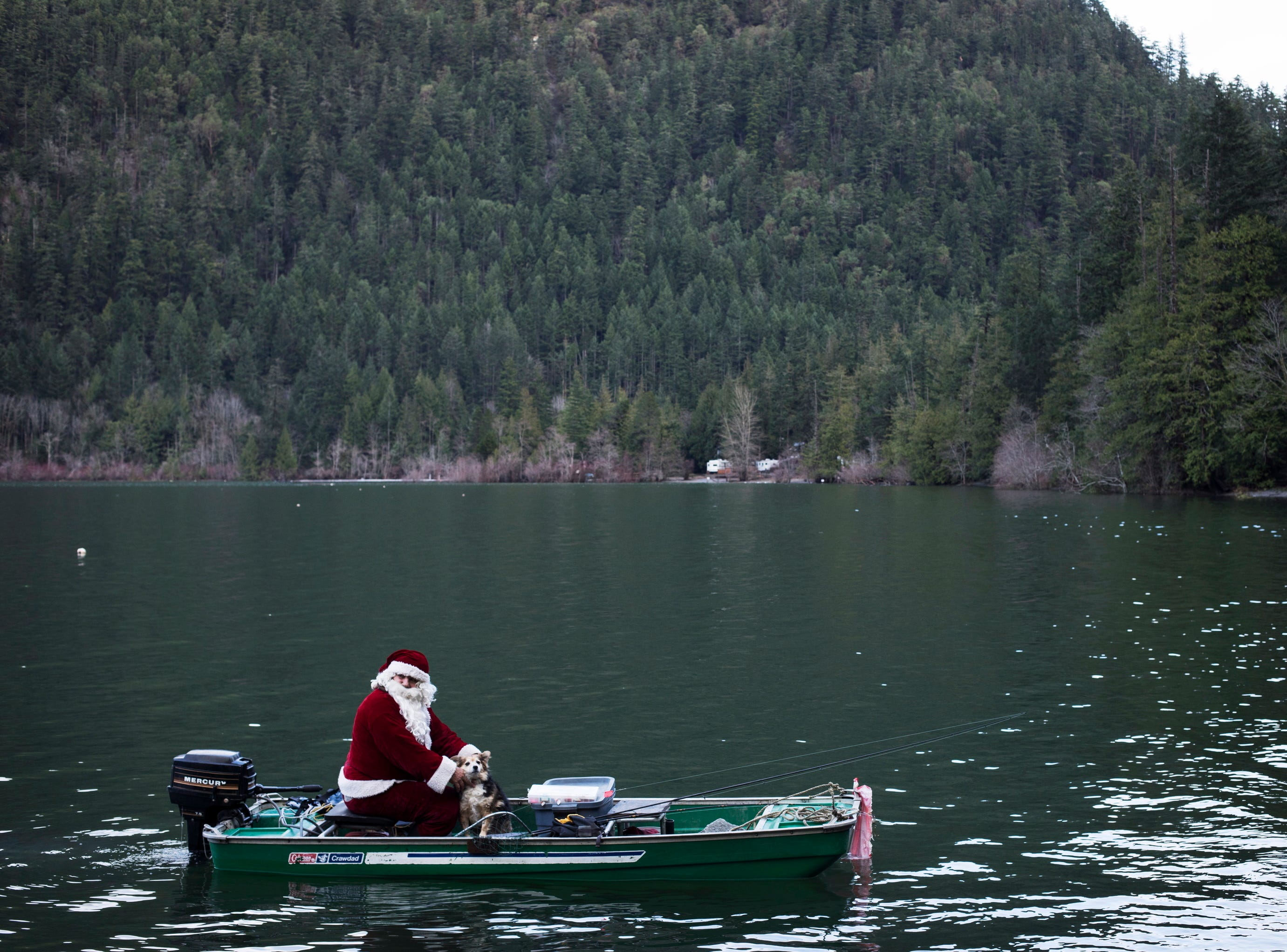 """Larvy Horvath, dressing up as Santa on Christmas Day for the past 15 years, rides a boat for fishing on Cameron Lake, near Port Alberni, British Columbia, Tuesday, Dec. 25, 2018. """"The kids like it when they go by,"""" he says, adding that the """"adults do too."""""""