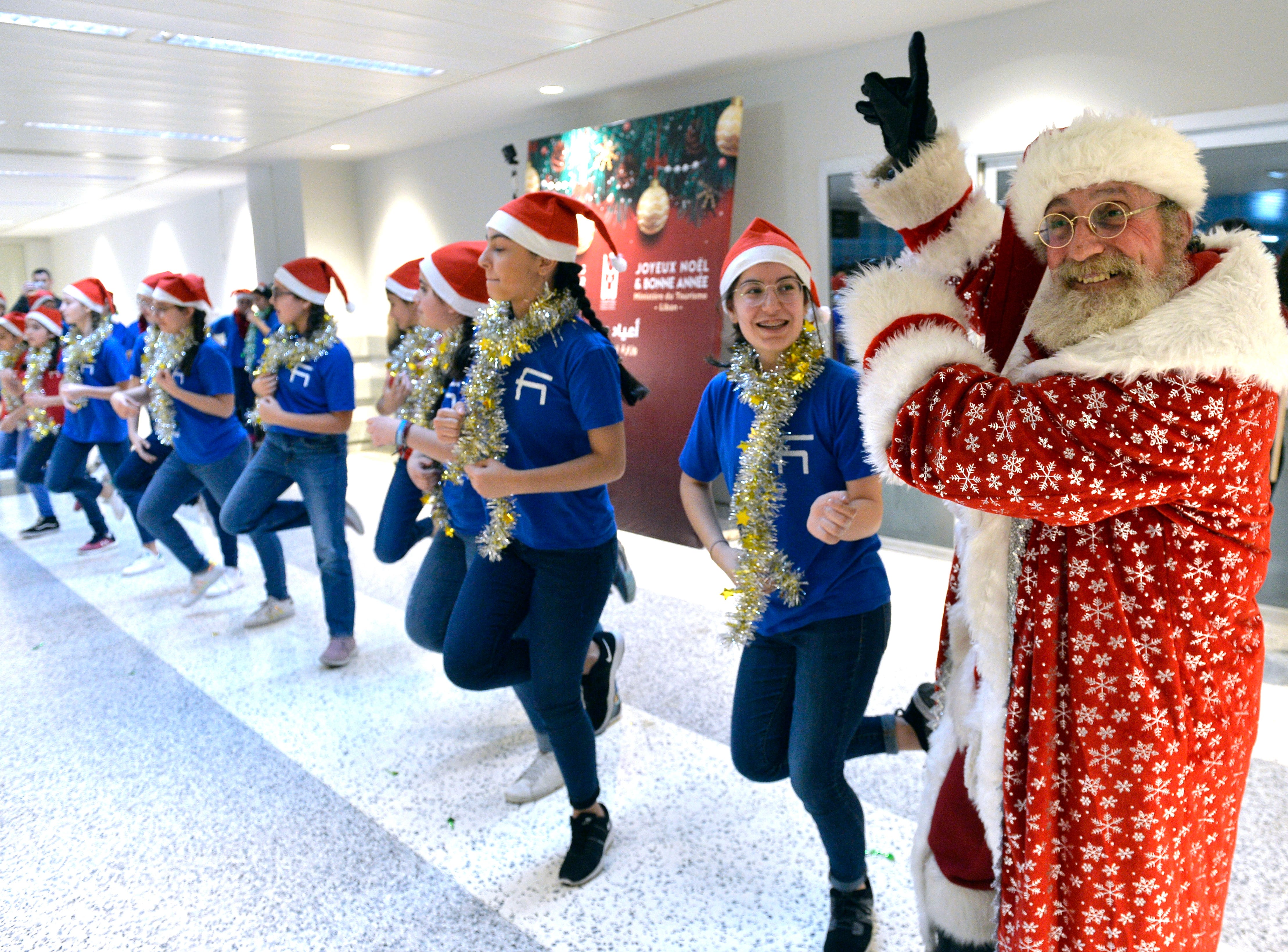 A man from Armenia dressed as Santa Claus dances with Lebanese and Armenian children upon his arrival at Rafik Hariri international airport in Beirut, Lebanon on Dec. 25, 2018. The man arrived in Beirut to celebrate the Armenian Christmas on January 6, 2019.