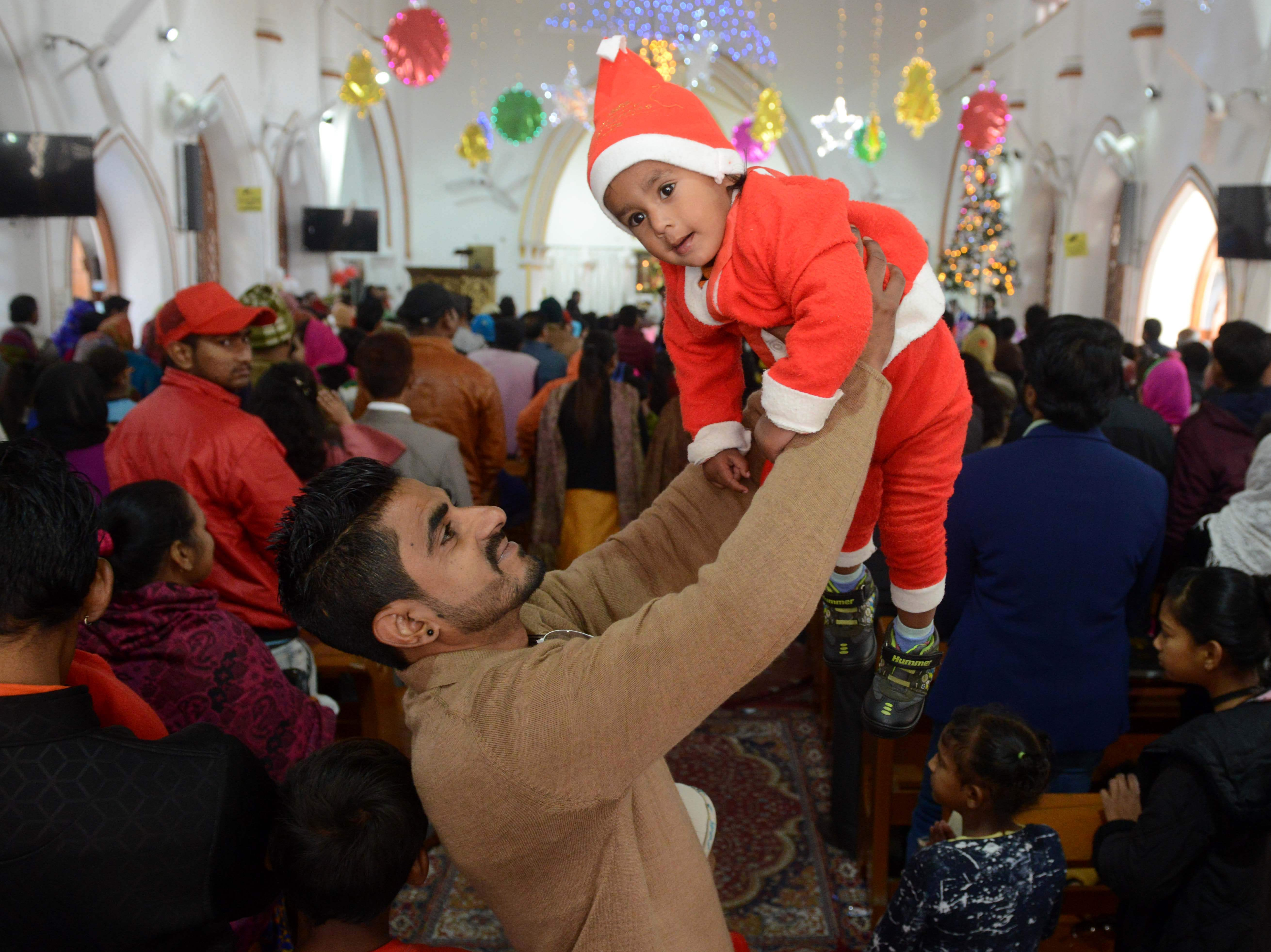 An Indian child dressed as Santa Claus is held up by his father at a service to mark Christmas Day at a church in Amritsar on Dec. 25, 2018. Despite Christians forming a little over two percent of the billion plus population in India, with Hindus comprising the majority, Christmas is celebrated with much fanfare and zeal throughout the country.
