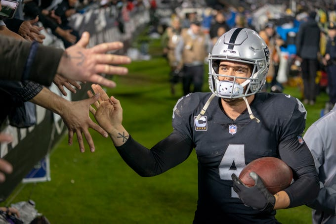 Raiders quarterback Derek Carr high-fives fans after the game against the Denver Broncos at Oakland Coliseum.