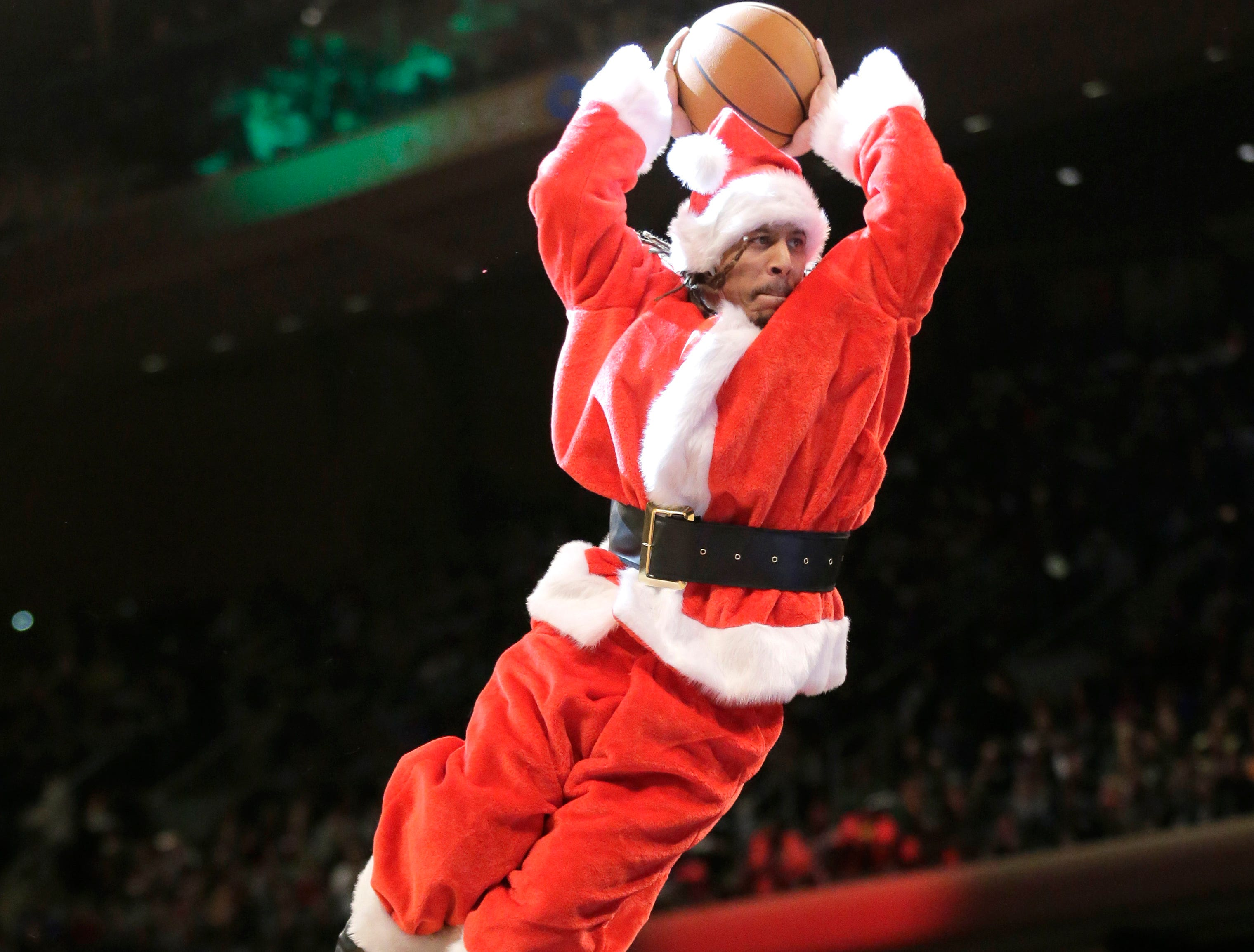 A performer dressed as Santa Claus dunks the ball during a break in the first half of the NBA basketball game between the New York Knicks and the Milwaukee Bucks, Tuesday, Dec. 25, 2018, in New York.